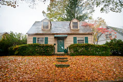 Small Cottage Home. Small cottage style home with leaves on the lawn in autumn Stock Photography