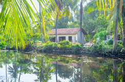 The small cottages on Hamilton`s Canal, Sri Lanka. The calm waters of Hamilton`s Canal reflect the small cottages and lush gardens of Wattala suburb of Colombo Royalty Free Stock Images