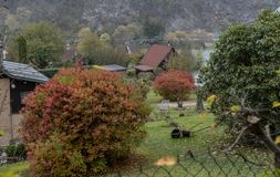 Small cottages in the middle of a garden between trees and bushes. With autumn leaves royalty free stock photo