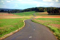 Small Country Road Winding through the Countryside. Small narrow country road paved and marked winding with S curves and gentle turns up a hill through the royalty free stock photography