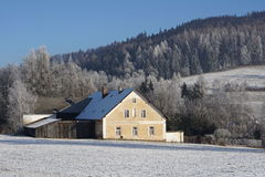 Small countryside house covered by snow in the valley between high mountains placed in Orlicke Hory Royalty Free Stock Image