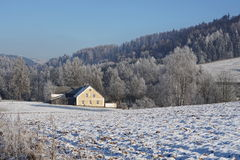 Small countryside house covered by snow in the valley between high mountains placed in Orlicke Hory Royalty Free Stock Photo