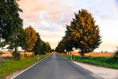 Small countryside road with trees on both sides photographed during sunset. With yellow and blue sky and dramatic lighting Stock Image
