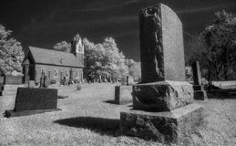 Small County Church with Cemetery and Headstones. Small Brick Country Church with Steeple next to Graveyard Cemetery with Headstones Black White stock photos