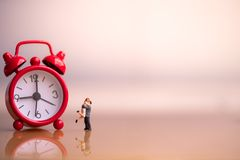 Small couple figures in love and red alarm clock. royalty free stock photo