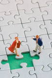 Small couple puzzle. A couple standing in front of a missing jigsaw puzzle piece Stock Photos