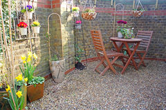 Small courtyard garden. Photo of a small courtyard garden with potted plants and patio table and chairs Stock Photo