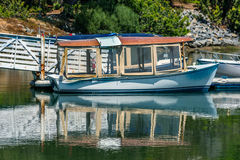 Small coveerd boat. Small covered boat moored at private pier Royalty Free Stock Photos