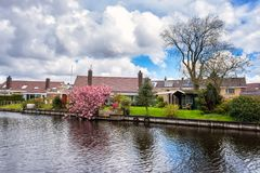Small cozy dutch village at springtime, beautiful daytime countryside landscape, Netherlands. Small cozy dutch village near water at springtime, beautiful royalty free stock images