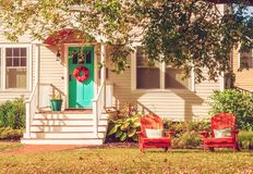 A small cozy wooden traditional American house with wooden chairs by the porch. Autumn sunny day. Vintage style. stock photo