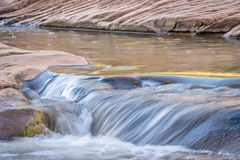 Small creek flowing over sandstone Royalty Free Stock Photography