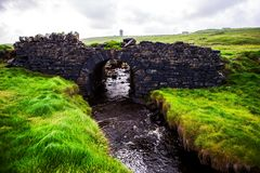 Small creek flowing under a stone bridge. With green grass meadows ireland nature rapid river rocks water stock photos