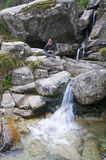 Small creek stream with waterfall and young woman Royalty Free Stock Photos