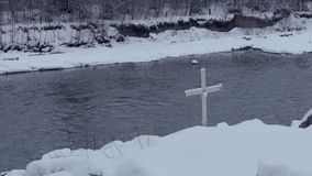 Small cross installed on a mountain riverbank in Bukovel in winter in slo-mo