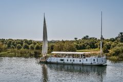 Small cruise-ship sailing up the river Nile. Small cruiser with two masts sailing up the river Nile. People relaxing on the top deck. Nile, Egypt, October 23 stock photo