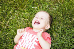 Small crying boy on grass. Small crying boy on  green grass Royalty Free Stock Photo