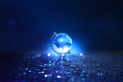 Small crystal globe in front of dark and dramatic light.global issues concept.  royalty free stock image