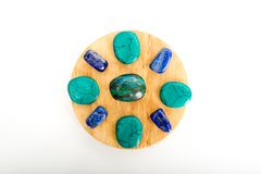 Small crystal healing grid with chrysocolla, howlite and lapis l. Azuli on wooden circle on white background Royalty Free Stock Photos