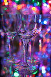 Small crystal liqueur glass with background of colorful lights Royalty Free Stock Images