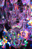 Small crystal liqueur glasses with colorful background and reflection. Small crystal liqueur glasses on background of colorful lights Royalty Free Stock Images