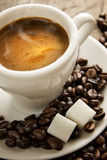 Small cup of black coffee on a brown background w Stock Photography
