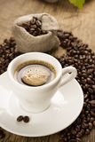 Small cup of black coffee with coffee beans Stock Photos