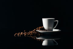 Small cup of black coffee on a dark background with coffee beans stock photography