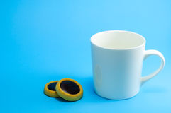 Small Cup Of Coffee On Blue Blackground. Empty White Small Cup Of Coffee And Cookies On Pastel Blue Background Stock Image