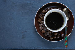 Small cup of espresso and aromatic coffee beans. Small cup of coffee espresso and aromatic coffee beans a positive charge and vigor on dark slate. top shot view Stock Images