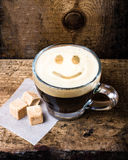 Small cup of espresso coffee in glass with smile pattern on old Royalty Free Stock Photography