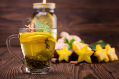 A small cup full of green lemon tea on a dark wooden background. A sweet tea cup next to carambola, ginger and mint. Copy space. royalty free stock image