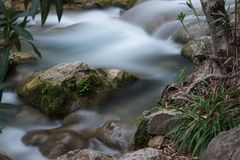 A small current creek with rapids and a stone with moss protruding from the water Stock Images