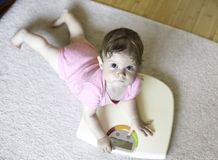 Small cute adorable baby girl on home scales royalty free stock image