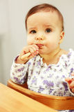 Small cute baby eating Stock Images
