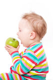 Baby eating green apple. Royalty Free Stock Images
