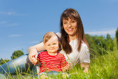 Small cute baby and his mummy sitting in meadow Royalty Free Stock Photos