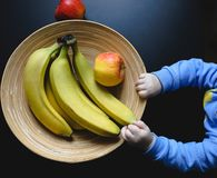 Small cute baby holding in hands original wooden plate with apples and bananas. Organic material of bowl with continuous lines on royalty free stock image