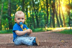 Small cute baby with nipple sits on the footpath in the dreamlike forest all alone. Little boy sitting on the ground. Royalty Free Stock Images