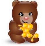 Small cute bear holding slice of honey. Cute brown bear sitting and holding slice of honey Stock Photography