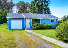 Small cute blue house with driveway and trimmed hedges. Stock Image