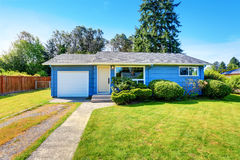Small cute blue house with driveway and trimmed hedges. Stock Photo