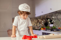 Small cute boy looking at the table with baking stuff. Royalty Free Stock Images