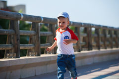 Small cute boy is walking in port Stock Photos
