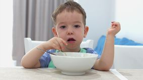 Small Cute Child is Sitting at a Table and eat his own oatmeal, the baby eats willingly. Concept Happy Childhood. stock footage