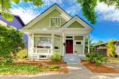 Small cute craftsman American house. Wth green and white and red door Royalty Free Stock Images