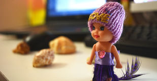 Small cute doll with purple dress and sweat hat. On office desk Royalty Free Stock Photography