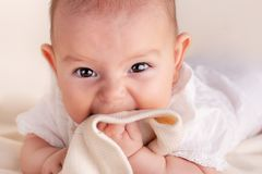 Small cute funny baby infant teething with face expression hands and fingers in mouth. Sore gums soothe close up portrait stock image