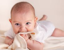 Small cute funny baby infant teething with face expression hands and fingers in mouth sore gums. Soothe stock photo