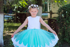Small cute girl in a blue and white dress and wreath raises the hem of her dress Royalty Free Stock Image