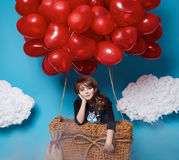 Small cute girl flying on red heart balloons Valentines day Stock Photo